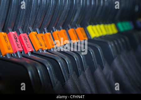 Hangers sorted by size in a clothing shopping center - Stock Photo