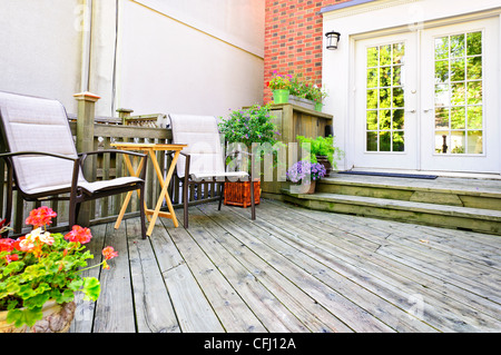 Wooden deck on house with chairs and french doors - Stock Photo