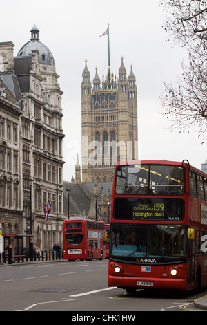 London Bus traveling past 10 downing street with Big Ben in the background - Stock Photo