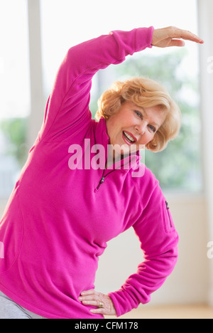 USA, New Jersey, Jersey City, Portrait of smiling senior woman stretching - Stock Photo