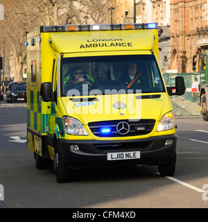 NHS London UK ambulance emergency SOS call National Health Service paramedic crew on board responding 999 call driving - Stock Photo