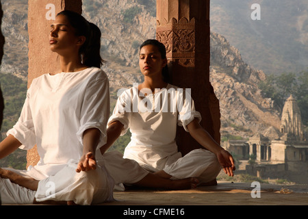 Women practising yoga in the abandoned town of Bhangarh, Alwar, Rajasthan, India, Asia - Stock Photo