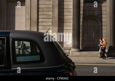 resting man seen through squared taxi cab window and approaching women outside the Bank of England. - Stock Photo