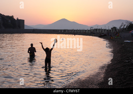 Family plays the ball against the setting sun over the horizon near Sveti Stefan. Budva. Montenegro - Stock Photo
