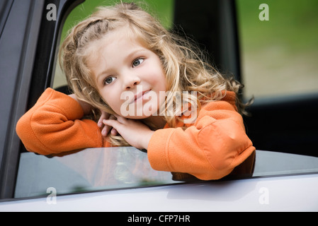 Little girl leaning out of car window, daydreaming, portrait - Stock Photo
