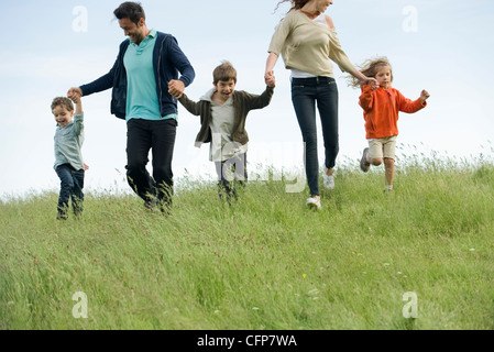 Family running hand in hand in field - Stock Photo
