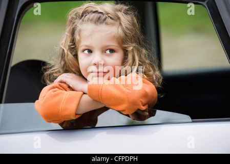 Little girl leaning out of car window, portrait - Stock Photo
