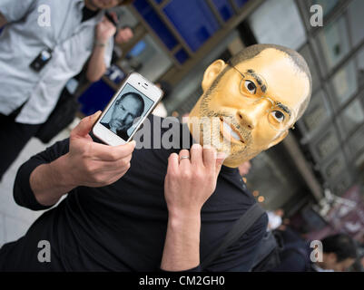 Japan, Tokyo. 21st September 2012. Japanese Apple Fan wearing Steve Jobs mask and holding his iPhone 4 waits in - Stock Photo