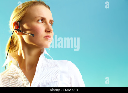 Image of pretty woman with headset on blue background - Stock Photo