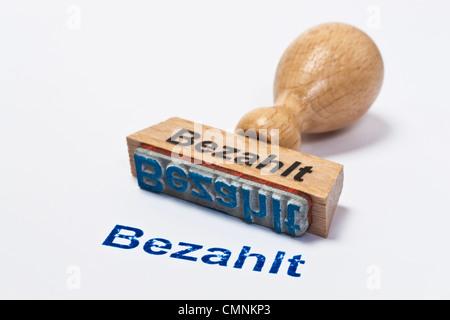 Detailansicht eines Stempels mit der Aufschrift Bezahlt | Detail photo of a stamp with inscription in German paid - Stock Photo