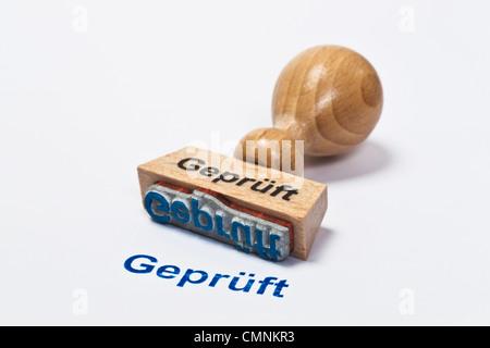 Detailansicht eines Stempels mit der Aufschrift Geprüft | Detail photo of a stamp with inscription in German checked - Stock Photo