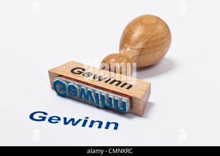 Detailansicht eines Stempels mit der Aufschrift Gewinn | Detail photo of a stamp with inscription in German profit - Stock Photo
