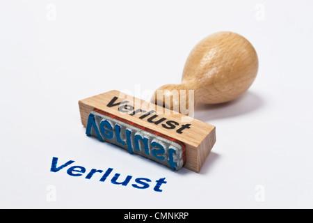 Detailansicht eines Stempels mit der Aufschrift Verlust | Detail photo of a stamp with inscription in German deficit - Stock Photo