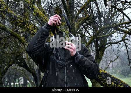 Man with bark peel mask under tree branches and falling snow in the woods. - Stock Photo