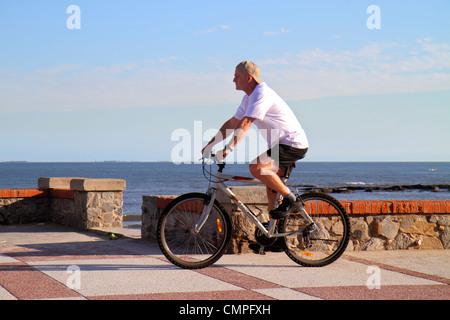 Uruguay Montevideo Rambla O'Higgins Hispanic man bicycle bike riding Rio de la Plata Atlantic Ocean Playa del Buceo - Stock Photo