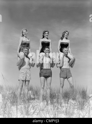 1950s 1960s THREE COUPLES AT BEACH ON DUNES WITH WOMEN IN IDENTICAL BATHING SUITS SITTING ON MEN'S SHOULDERS - Stock Photo