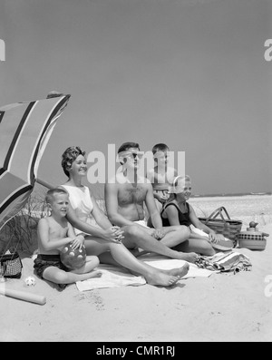 1960s FAMILY PORTRAIT MOTHER FATHER DAUGHTER AND TWO SONS SITTING ON BEACH UNDER UMBRELLA - Stock Photo
