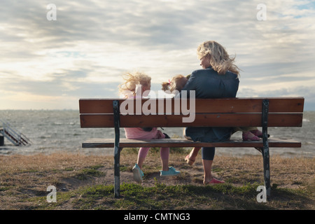 Woman and daughters (4-7) sitting on bench at beach - Stock Photo