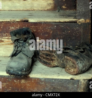 Worn old work boots on wooden stairs - Stock Photo