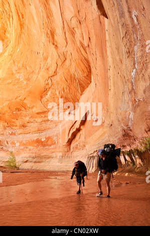 Mother and son backpacking in Coyote Gulch, a tributary of the Escalante River in Southern Utah. - Stock Photo