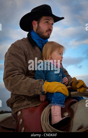 A cowboy and his daughter on horseback at ranch in northeastern Wyoming - Stock Photo