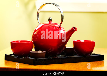 Red tea pot on black tray in the kitchen - Stock Photo