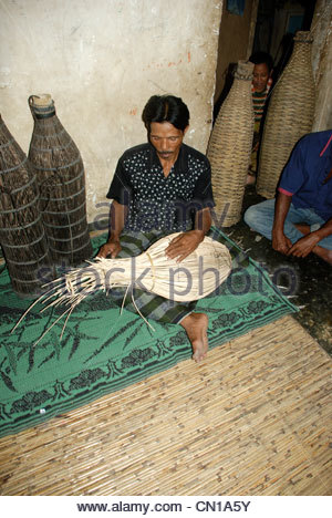 Man seated on mat e house making fish traps from cane and bamboo and arenga palm Cakranegara Lombok Barat NTB Indonesia - Stock Photo