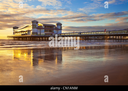Golden evening light falls on the Grand Pier at Weston-Super-Mare, Somerset, England, UK eflected in the wet sand - Stock Photo