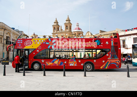 Red double decker open top tourist city sightseeing bus in Marsaxlokk, Malta - Stock Photo