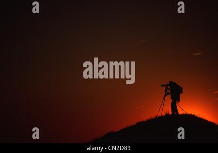 Silhouette of Photographer at Sunset, near Eagle Butte, Grasslands National Park, Saskatchewan - Stock Photo