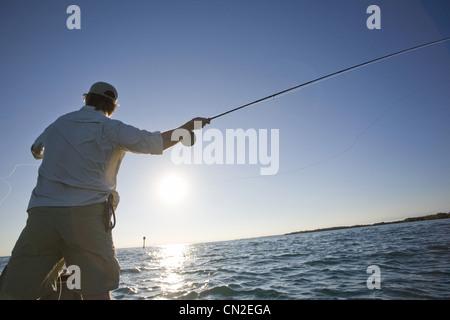 Man Casting Fishing Rod From Boat, Florida Keys, USA - Stock Photo