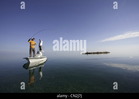 Two Men Fly Fishing in Boat Near Shipwreck, Florida Keys, USA - Stock Photo