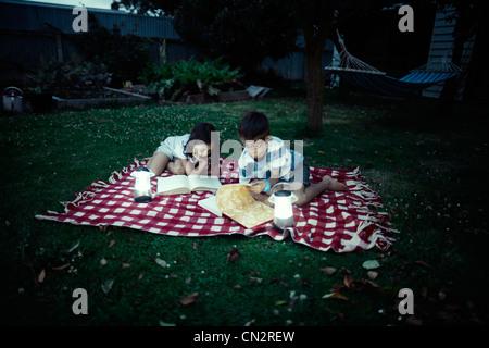 Children read books by lantern light on blanket in garden in evening. - Stock Photo