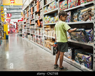 Boy decides on toy to buy with his pocket money in a toy store. - Stock Photo
