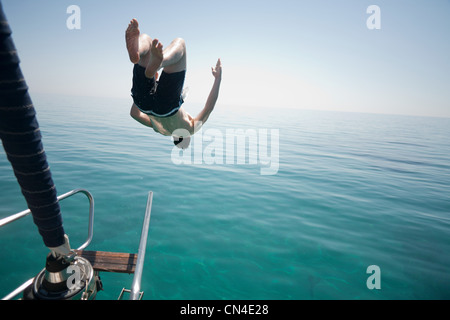 Man jumping head first into the sea - Stock Photo