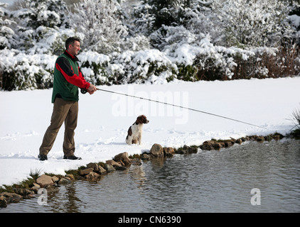 Man and his dog fishing at Lochter fishery near Oldmeldrum in Aberdeenshire, Scotland, UK - Stock Photo