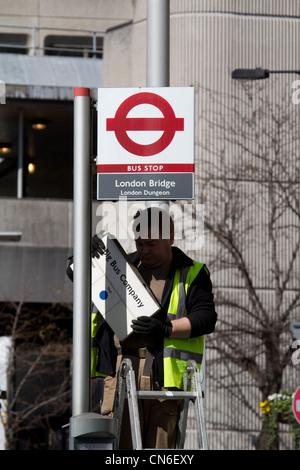 workman fixing information to bus stop for big bus company, London Bridge, London - Stock Photo