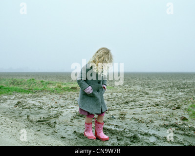 Girl wearing rainboots on beach - Stock Photo