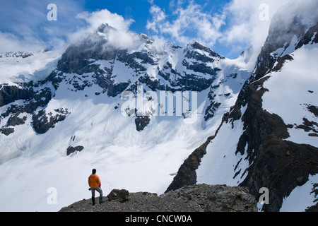 Female hiker views the snowcovered Bellicose Peak, Rumble Pass, Chugach State Park, Southcentral Alaska, Summer - Stock Photo