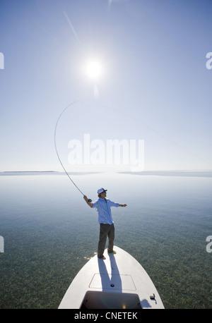 Man Fly Fishing From Bow of Boat, Florida Keys, USA - Stock Photo