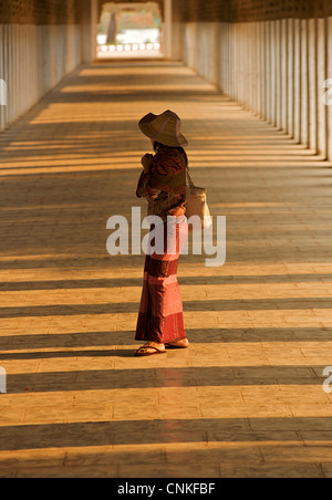 Burmese woman in the corridor at Shwezigon Pagoda, Bagan. Burma. Model Released. - Stock Photo