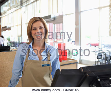 Cashier standing at till in supermarket - Stock Photo