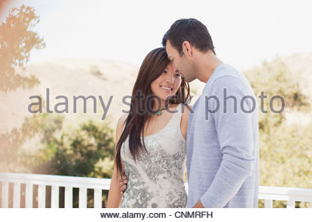 Smiling couple hugging outdoors - Stock Photo