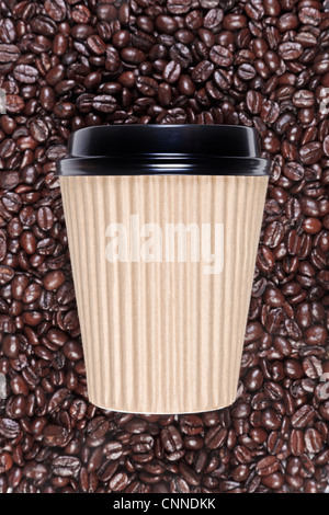 Photo of a disposable paper coffee cup with a mixture of arabica and robusta beans in the background. - Stock Photo