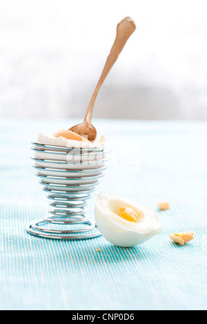 Close-up of a hard-boiled egg in a silver spiral eggcup - Stock Photo