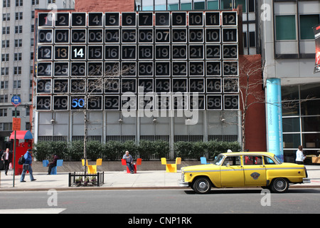 Iconic yellow New York taxi cab parked in front of a giant clock in Manhattan. USA - Stock Photo