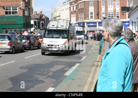two leicestershire police vans travel through a busy town - Stock Photo