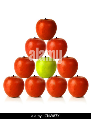 red apples on a pyramid shape with one green apple in the middle, be different - Stock Photo