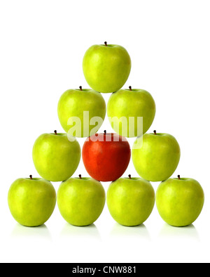 green apples on a pyramid shape with one red apple in the middle, be different - Stock Photo
