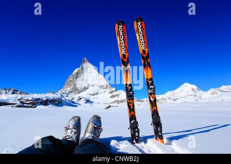 feet with hiking boots and skis in front of Matterhorn, Switzerland, Valais, Zermatt - Stock Photo